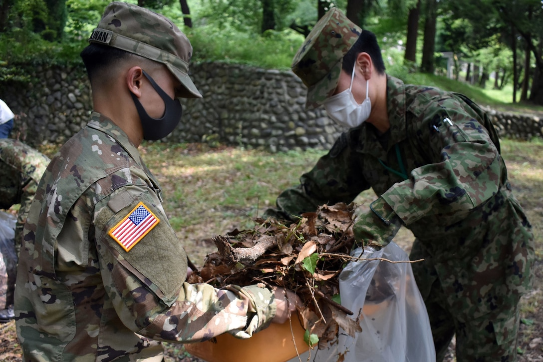 Two soldiers wearing masks put debris in a large bag.