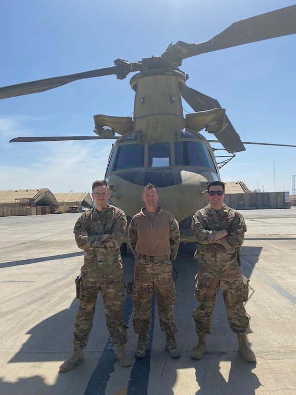 Three Airmen posing in from of a U.S. Army helicopter