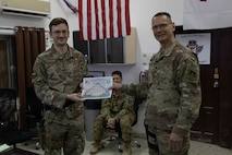 Airman poses with certificate with commander