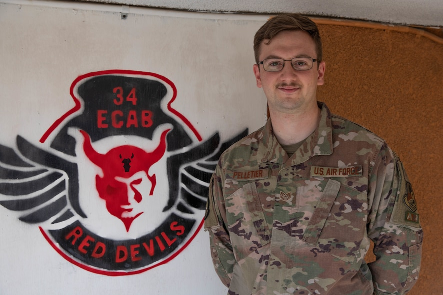 Airman stands next to image of 34th ECAB unit seal on the wall behind him