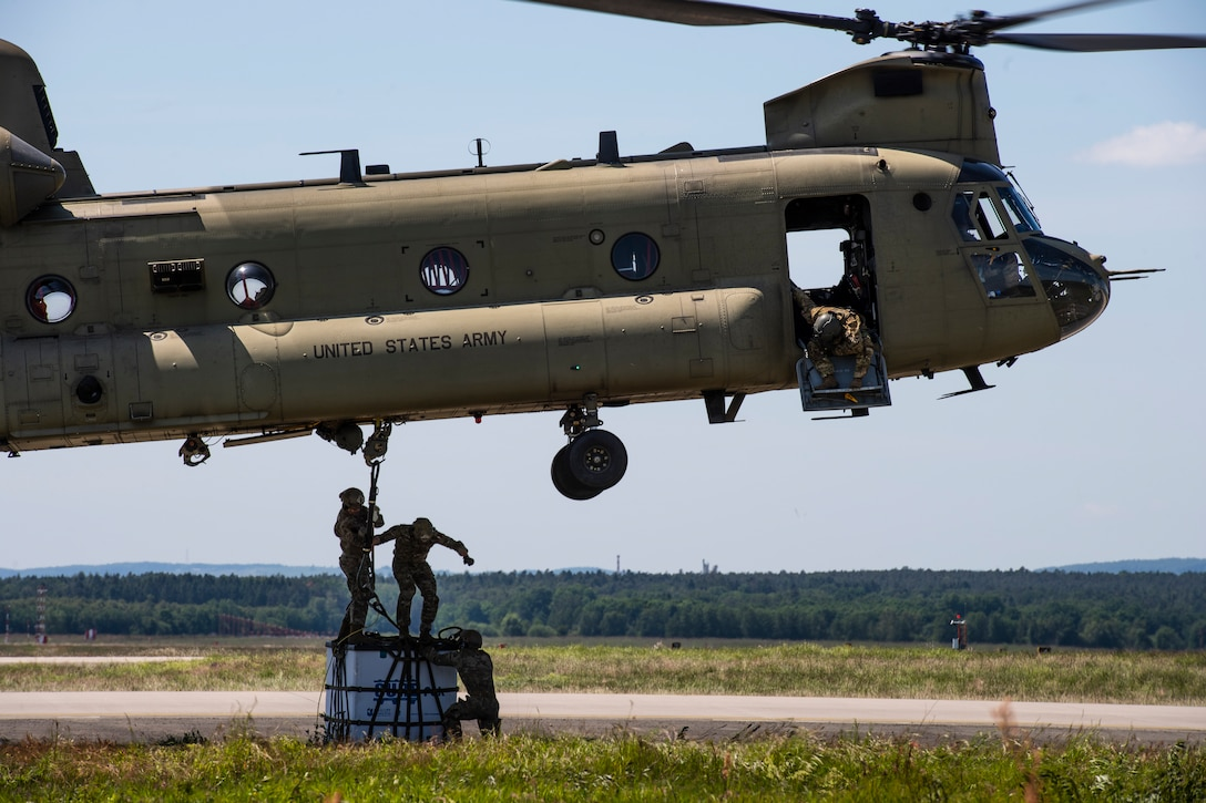 Photo of Airmen sling loading cargo onto a helicopter