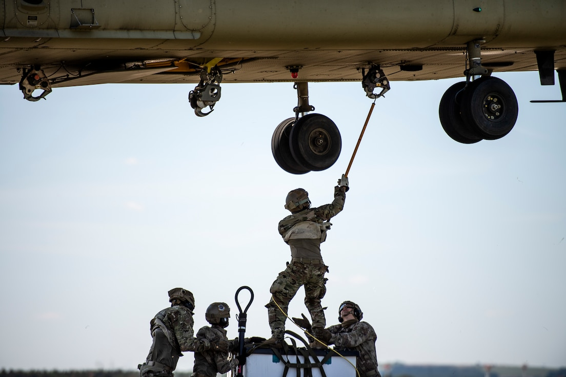 Photo of Airmen sling loading cargo to a helicopter