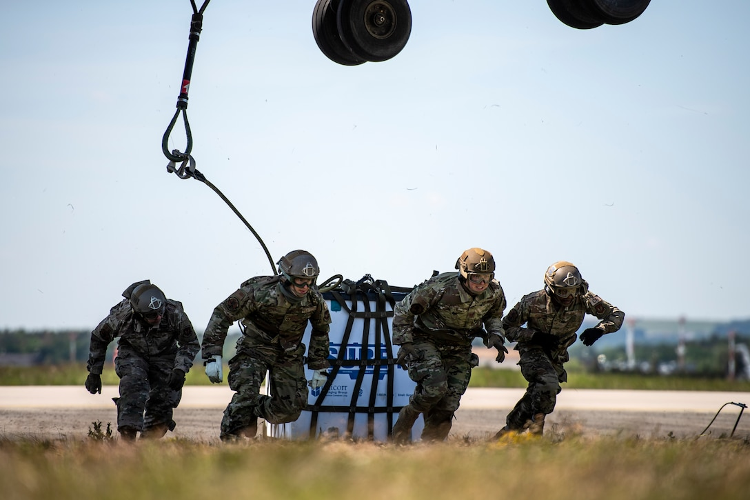Photo of Airmen running away from a helicopter