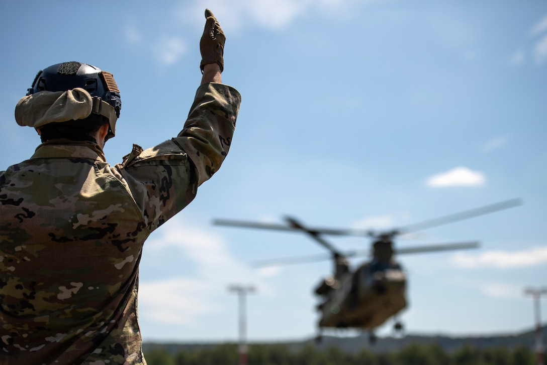 Photo of Airman directing helicopter