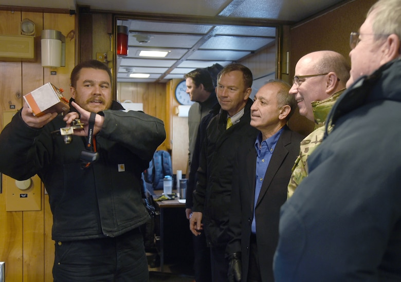 John Semands, an electronics engineer with the 76th Software Engineering Group, explains the functionality of fiber optic transmitters within the data acquisition system to visitors from the Senior EMP Working Group during a tour of the Compass Rose Testing Facility Jan. 22. The facility was running hardness maintenance/hardness surveillance electromagnetic pulse testing on a B-52H Stratofortress from the 2nd Bomb Wing, Barksdale Air Force Base, Louisiana. (U.S. Air Force photo/Kelly White)