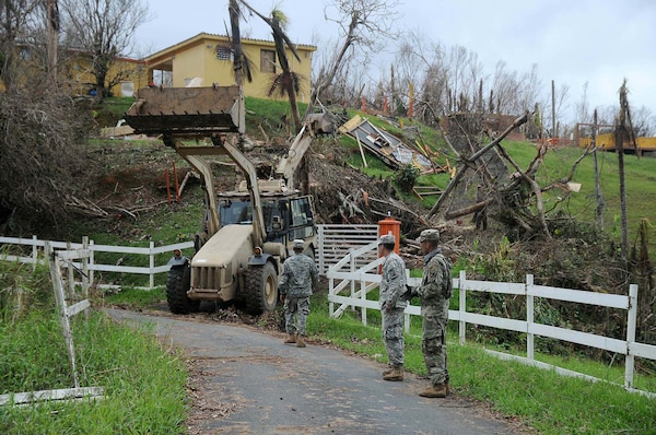 Citizen-Soldiers of the 190th Engineer Battalion, 101st Troop Command, Puerto Rico Army National Guard, clear debris in Cayey Sept. 30, 2017, after Hurricane Maria caused heavy damage throughout the region. Fallen trees, power lines and debris kept the community isolated for days.