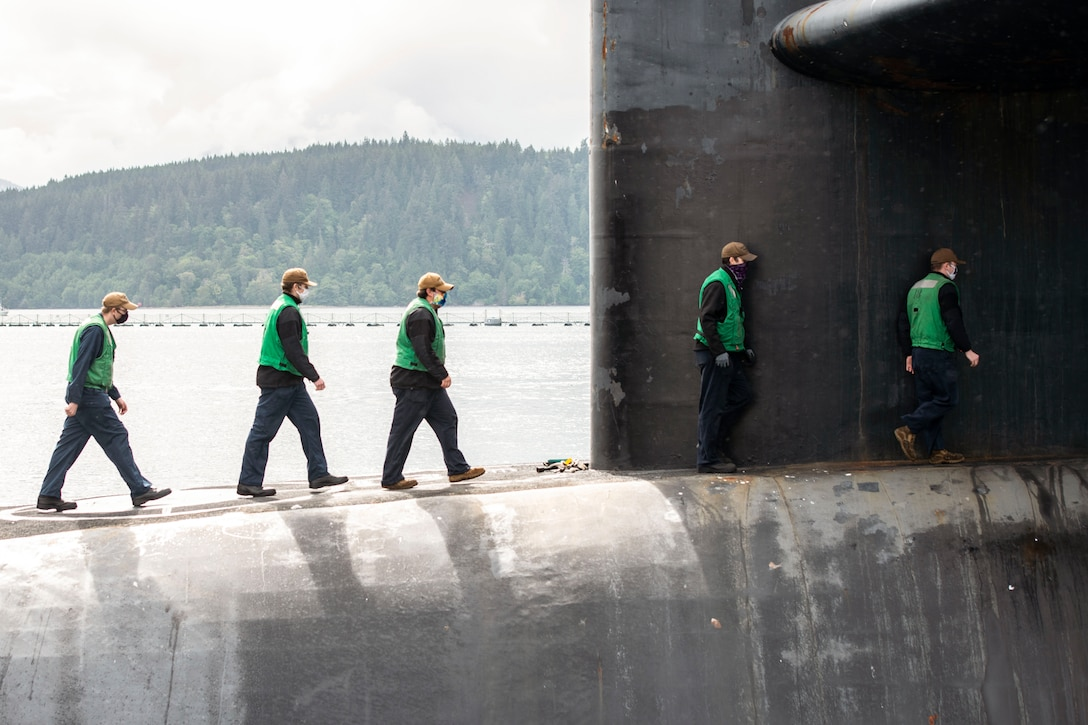 Sailors wearing green vests and protective gear walk in a line.