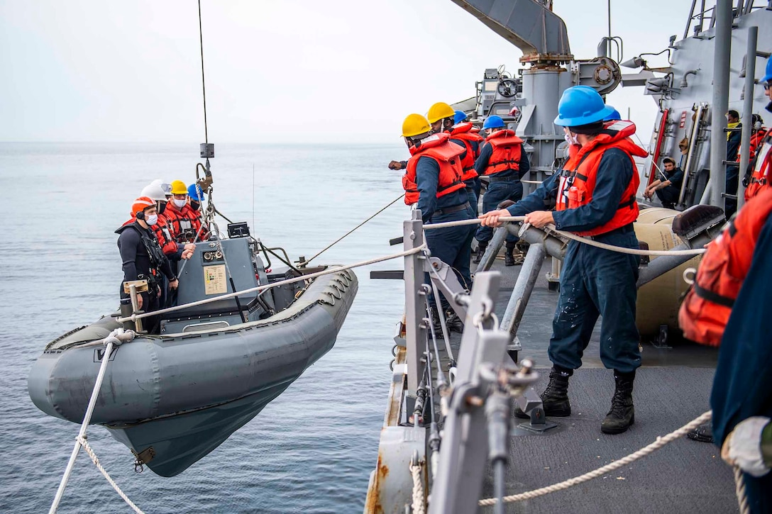 Sailors stand in an inflatable boat next to a ship as it lowers into water; other sailors stand on the ship watching.