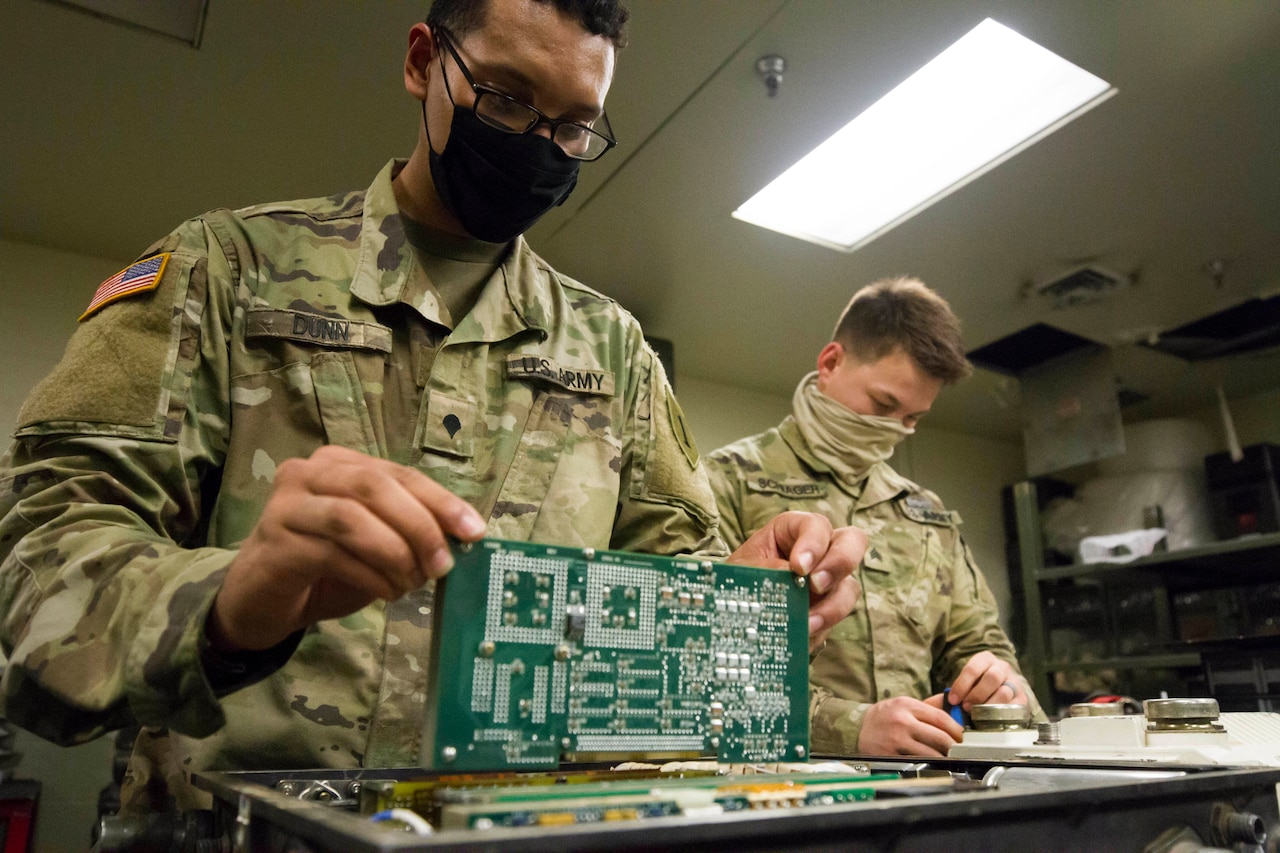 Soldiers working while wearing personal protective equipment.