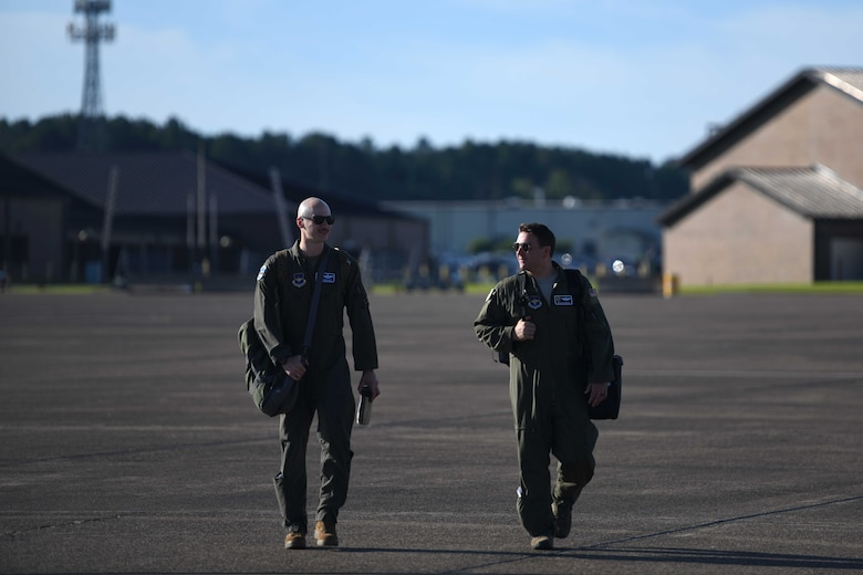 Maj. John Rebolledo and Nathan Eldredge, 62nd Airlift Squadron instructor pilots, walk towards a C-130J Super Hercules at Little Rock Air Force Base, Arkansas.