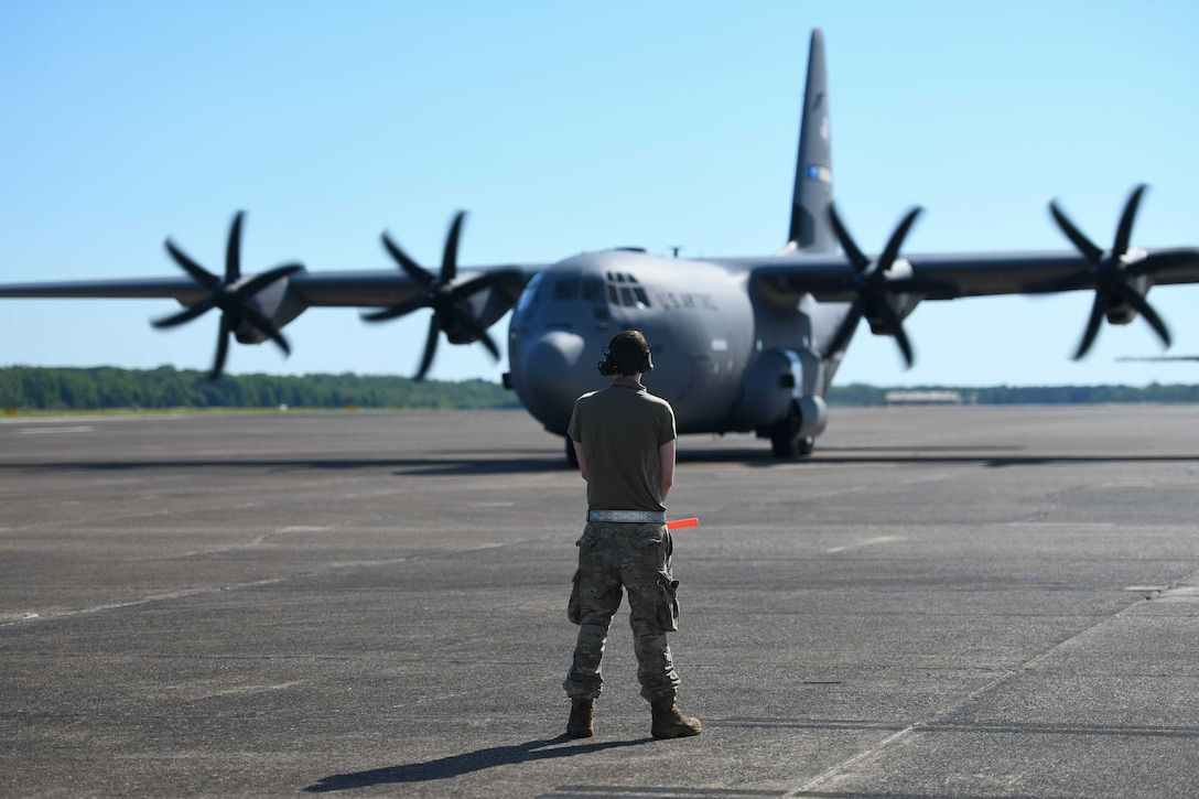 An Airmen from the 314th Aircraft Maintenance Squadron prepares to marshal a C-130J Super Hercules to the runway at Little Rock Air Force Base, Arkansas.