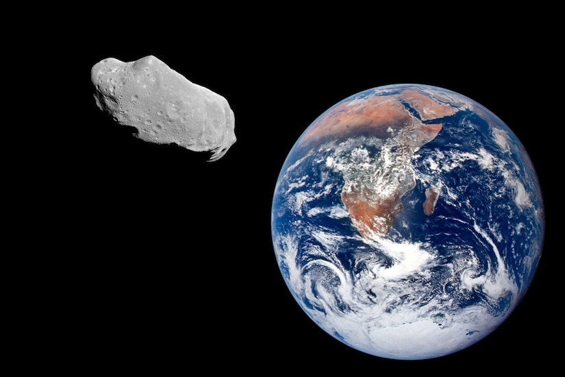 A large rock floats in space above the Earth.