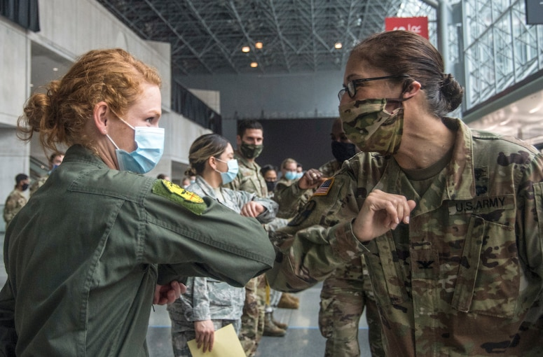 A soldier and an airman wearing face masks elbow-bump each other in a large room.
