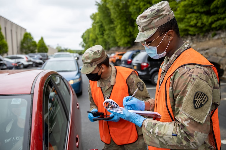 A soldier talks to a driver in a car while a second soldier takes notes.