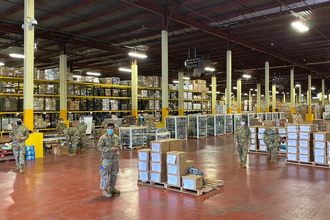 Service members work in a large warehouse.