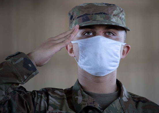 service member saluting while wearing a face covering
