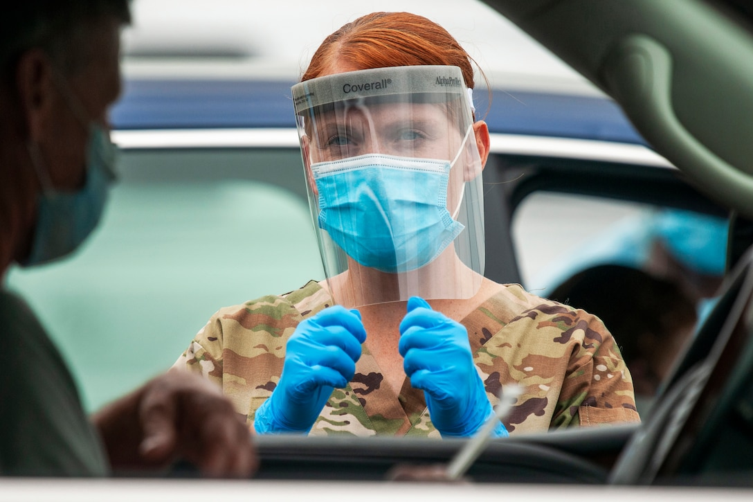 A guardsman gives instructions to drivers during a drive-thru coronavirus testing mission.