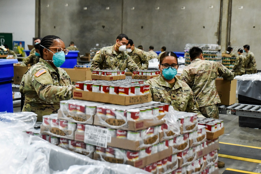 Army National Guardsman in masks help assemble emergency food kits.