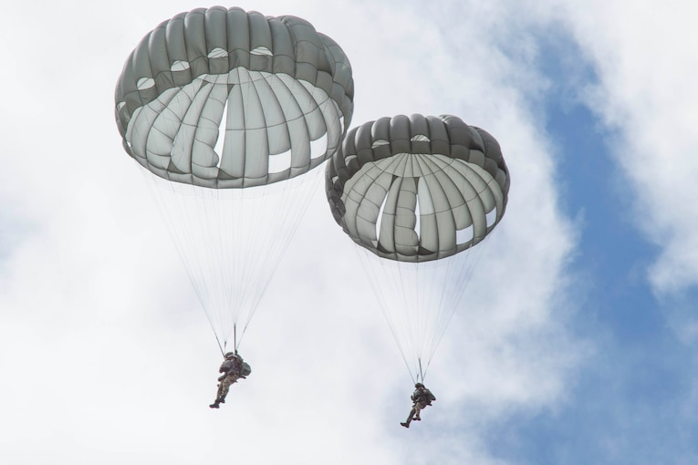 Two airmen descend in the sky wearing parachutes.