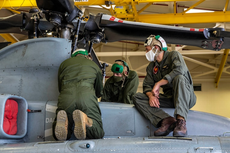 hree Marine Corps students work on a helicopter.