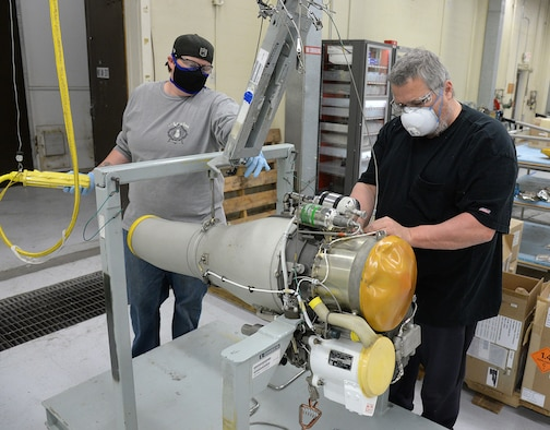 582 Missile Maintenance Squadron liquid engine rocket fuel mechanics, Jennifer McClellan (left) and Kevin O'Donnell, maintain their social distance while preparing an F-107 turbofan engine for placement into a shipping container on Apr. 28, 2020, at Hill Air Force Base, Utah.