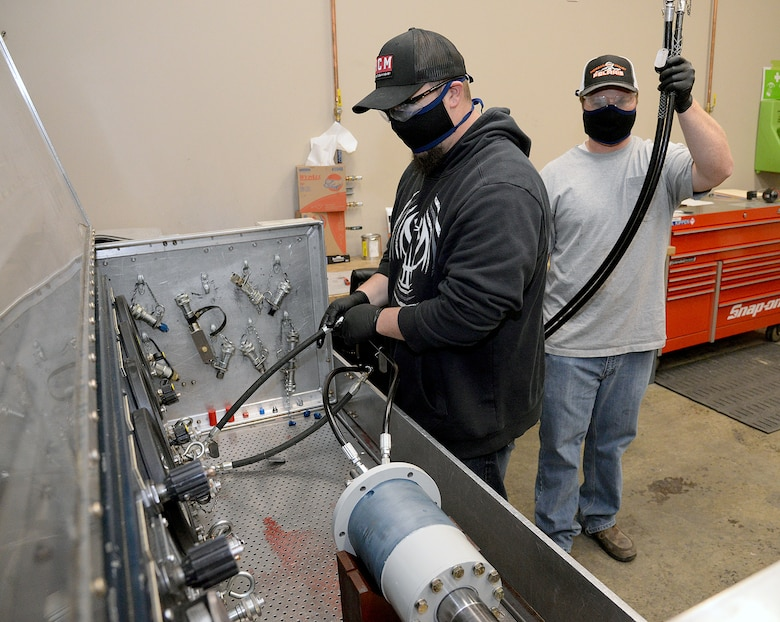 Shadd Straw and Garrett Kippen (left to right), 581 Missile Maintenance Squadron powered support system mechanics, wear their protective face coverings while they work to connect hydraulic lines from a test stand to a loading mechanism on Apr. 28, 2020, at Hill Air Force Base, Utah.