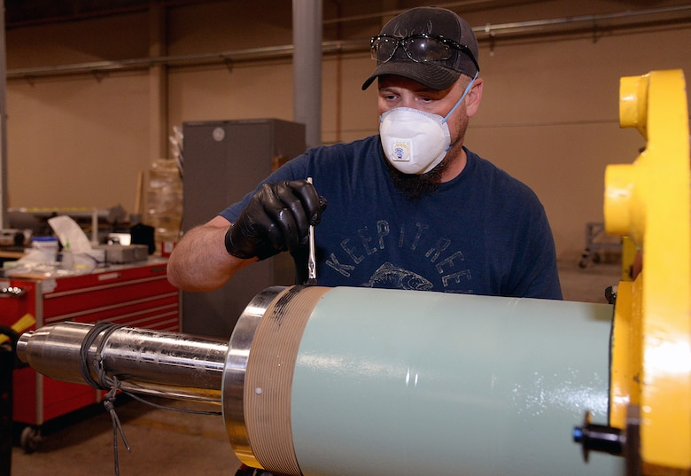 Clint Struchen, 581 Missile Maintenance Squadron powered support system mechanic, applies thread lubricant to the end of a launch control center shock isolator on Apr. 28, 2020, at Hill Air Force Base, Utah. Each LCC has four isolators used to support the floor where missile launch control personnel perform their duties.  (U.S. Air Force photo by Alex R. Lloyd)