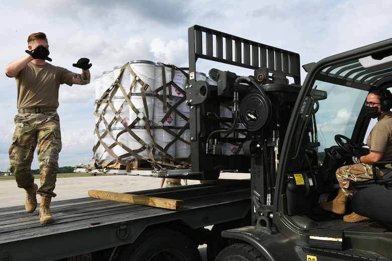 Photo shows one Airmen directing another on a forklift while she lowers a pallet containing numerous buckets to a flatbed truck.