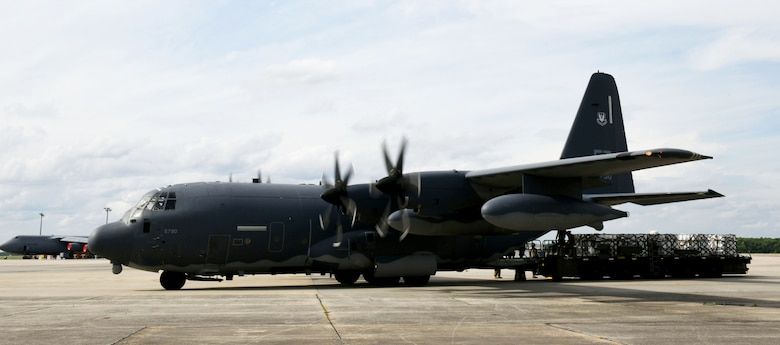Photo shows C-130 aircraft with truck behind the cargo end of the plane containing pallets with buckets.