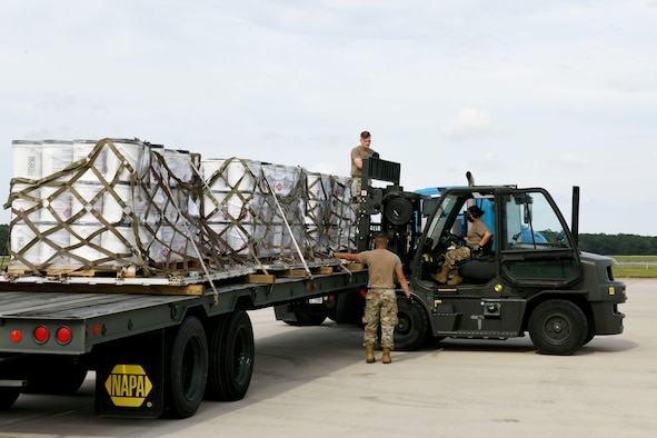Photo shows three Airmen working on a small flat bed truck loading five pallets of buckets.