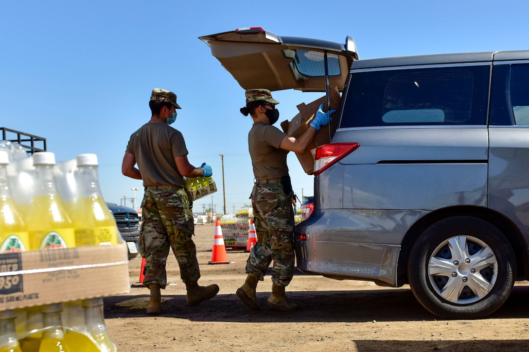 Two soldiers load food into the back of a minivan as pallets of bottled juice sit nearby.