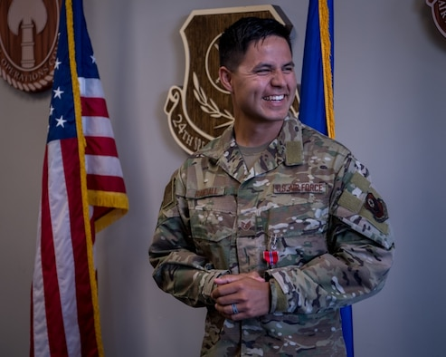 An airman smiles after receiving an award