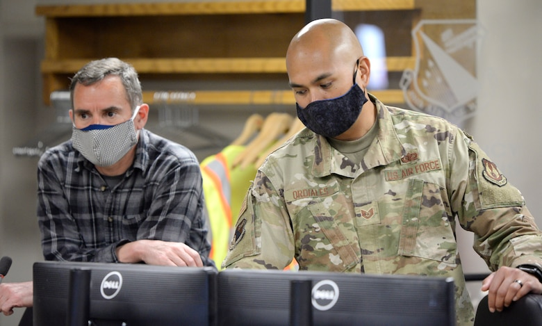 William Neitzke, left, 88th Air Base Wing Incident Command Center director of safety and planning and Tech. Sgt. Jeremy Ordiales, ICC section chief, admin cell, listen to a daily conference call with Col. Thomas P. Sherman, 88 ABW commander, while monitoring the COVID-19 pandemic at Wright-Patterson Air Force Base, Ohio, May 5, 2020. The continued use of face coverings, proper sanitation procedures and social distancing practices has enabled Wright-Patterson Air Force Base to complete three weeks of Phase I of its Return to Full Capacity plan without an increase to the number of positive COVID-19 cases reported by base medical center officials.  (U.S. Air Force photo/Ty Greenlees)