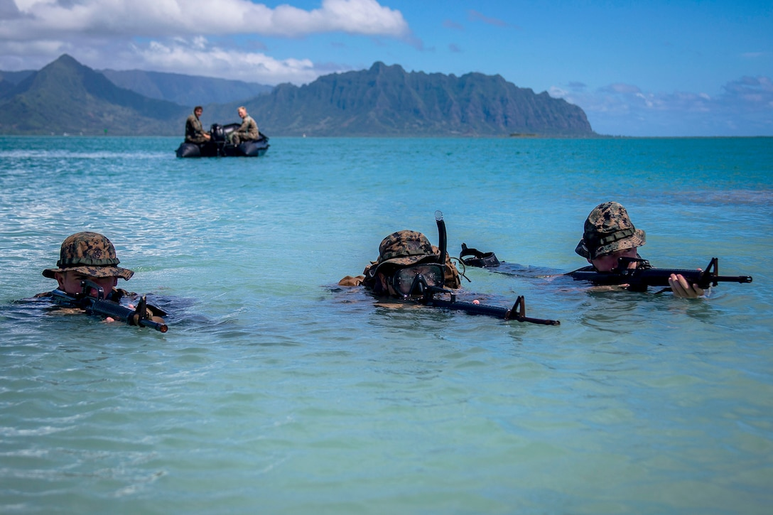 Three Marines holding weapons stand with their heads just above water.