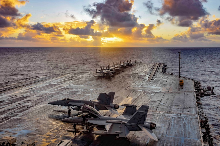 An aircraft carrier with several military jets floats on the water at twilight.