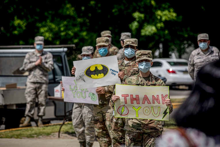 "Airmen wearing masks hold up handwritten ""Thank You"" signs as a civilian walks toward them outside a building."