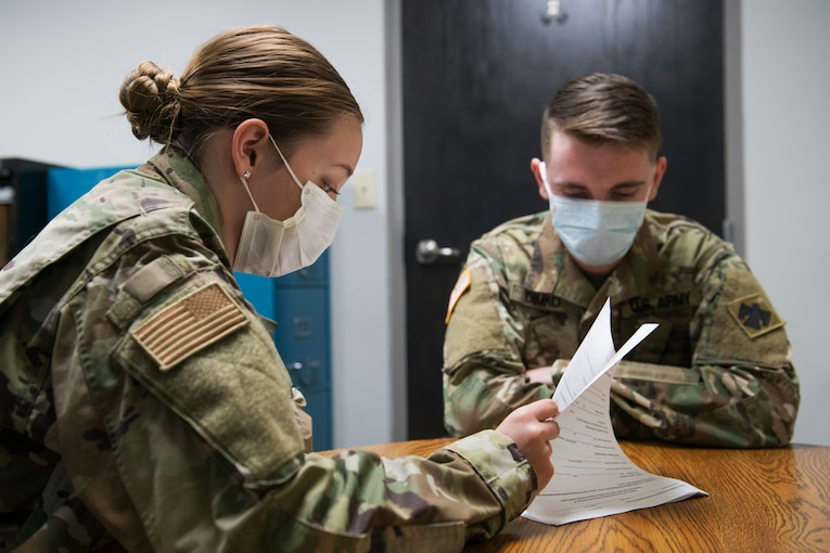 An airman and a soldier, both wearing masks, review documents for COVID-19 contract tracing.