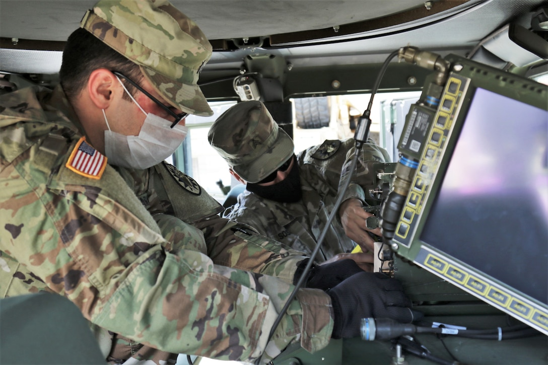Two Army soldiers in masks work on a radio system while in a Humvee.
