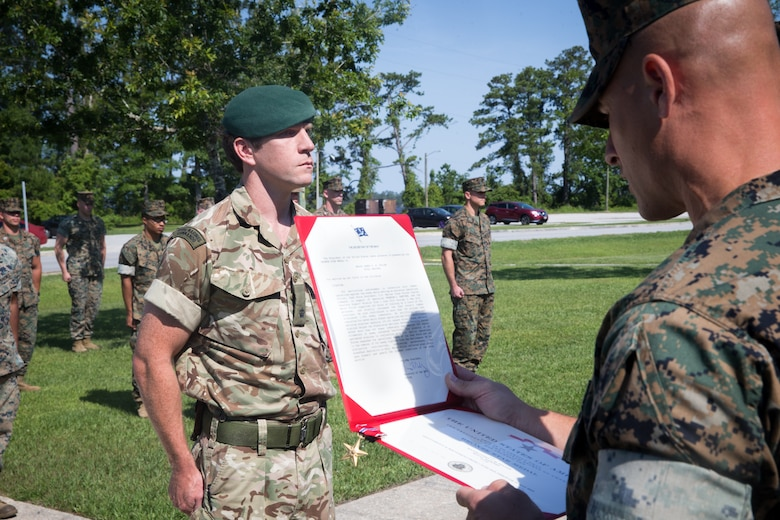 U.S. Marine Corps Sgt. Maj. David Elliott, right, sergeant major of 2nd Marine Regiment, 2nd Marine Division, reads the Bronze Star Medal award citation for British Royal Marine Maj. James A. Fuller, the future operations officer with 2nd Marine Regiment, at Camp Lejeune, North Carolina, June 3, 2020. Fuller received the Bronze Star for his distinctive contributions and efforts as the assistant operations officer with Task Force Southwest 19.1, U.S. Marine Corps Forces Central Command in Afghanistan. Fuller directly increased TSFW's combat effectiveness and operational reach in Helmand Province. (U.S. Marine Corps photo by Lance Cpl. Jacqueline Parsons)