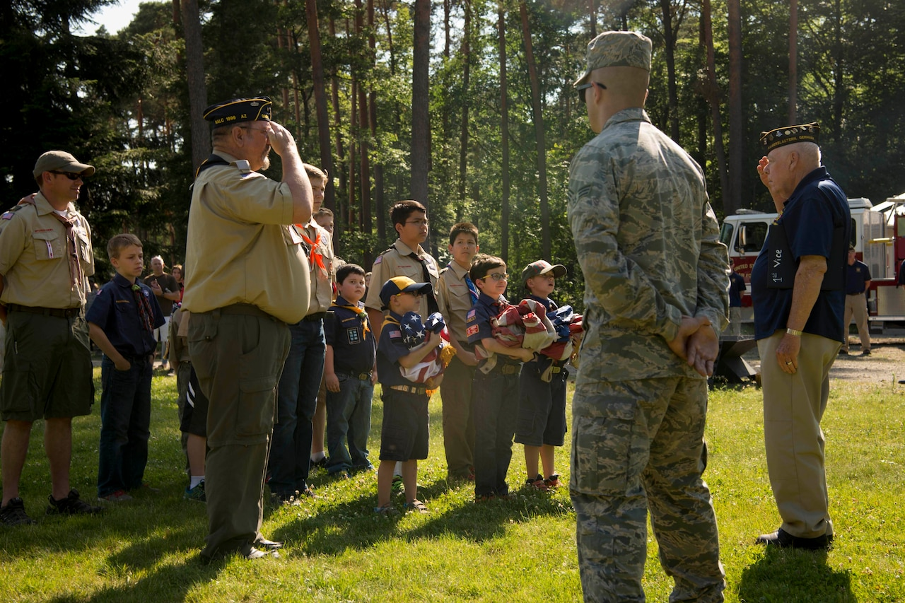 An airman stands by as a scout leader salutes an older veteran. Several young men stand with them, three of whom are holding unserviceable flags.
