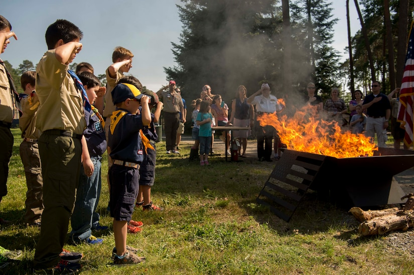 Several boys in Boy Scout uniforms salute a blazing fire pit as adults do so in the background.