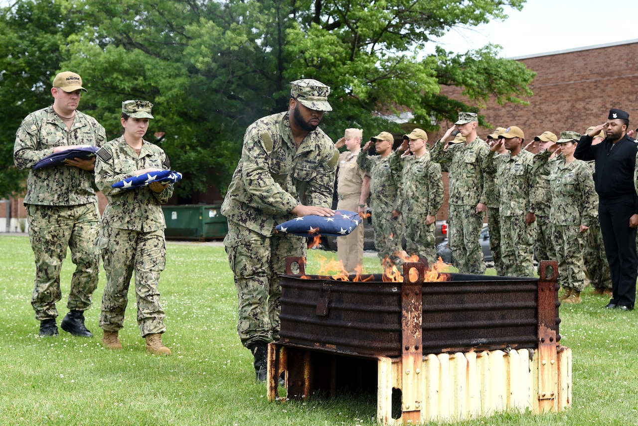An airman places a folded flag into a fire pit as others nearby salute.