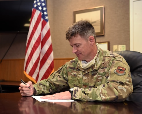 U.S. Air Force Col. Thomas Coakley, 17th Training Group commander, shows how he signs an articulation agreement amendment to an existing 2013 agreement between Angelo State University and the 17 TRG, during the COVID-19 pandemic, in the Brandenburg Hall on Goodfellow Air Force Base, Texas, June 2, 2020. The amended agreement allowed the 14N Intelligence Officer course graduates to transfer up to 12 semester hours towards three different ASU graduate programs for free. (U.S. Air Force photo by Airman 1st Class Abbey Rieves)