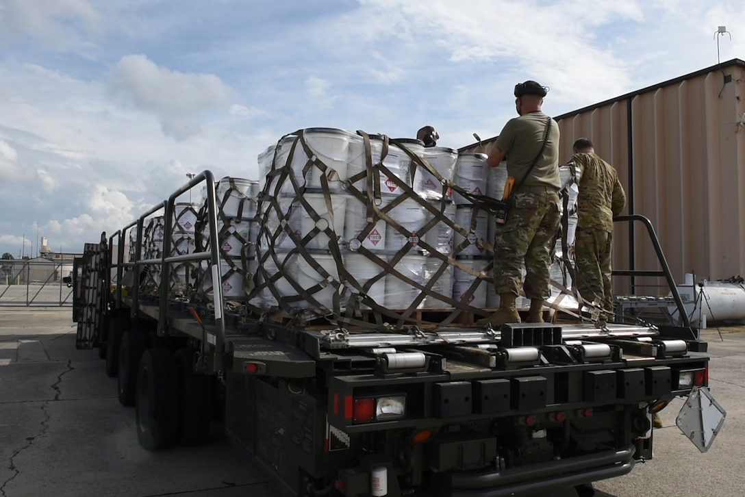 Photo of Airman removing net sets from hand sanitizer pallets