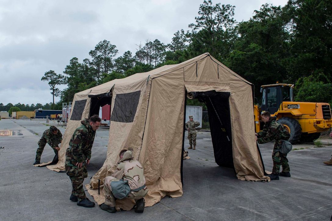 Photo of students of the Multi-Capable Airmen course setting up a tent.