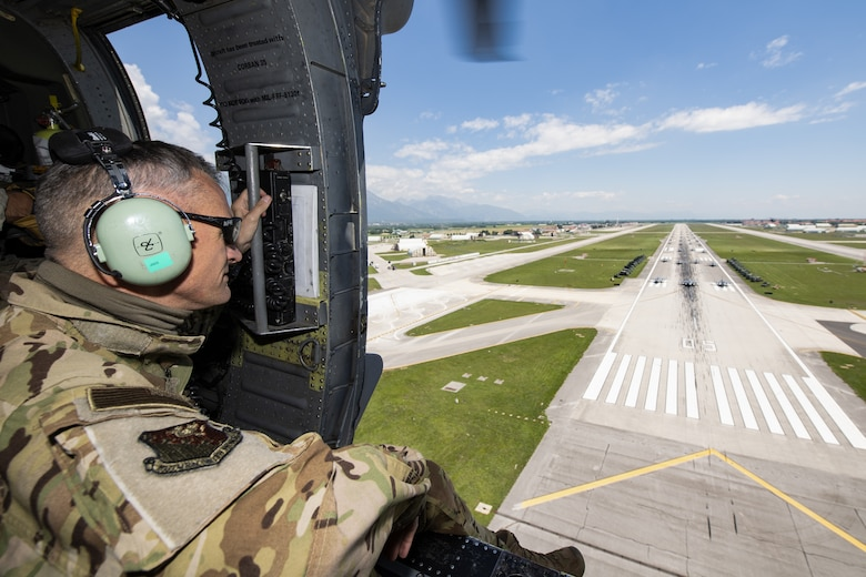 U.S. Air Force Brig. Gen. Daniel T. Lasica, 31st Fighter Wing commander, overlooks an elephant walk while on an HH-60G Pave Hawk helicopter over Aviano Air Base, Italy, June 1, 2020. Elephant walks are a show of force, demonstrating the might and power of the U.S. Air Force and its bases. (U.S. Air Force photo by Airman Thomas S. Keisler IV)
