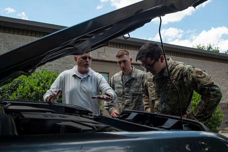 Photo of an Airman explaining how to search a vehicle.
