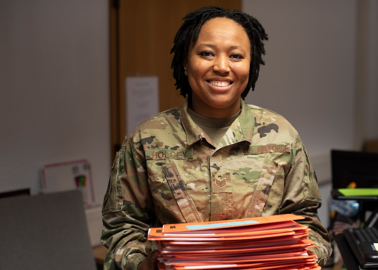 U.S. Air Force Staff Sgt. Jasmine Holcey, 786th Force Support Squadron relocations supervisor, poses for a photo holding a day's worth of personnel out-processing folders at Ramstein Air Base, Germany, June 1, 2020.