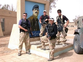 These four OSI agents in front of a Saddam Hussein portrait, were the first OSI agents in Iraq at the start of operation IRAQI FREEDOM. (U.S. Air Force photo)