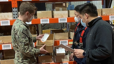 Three workers in face masks review materials pulled from a bin in front of a warehouse shelf lined with similar bins.